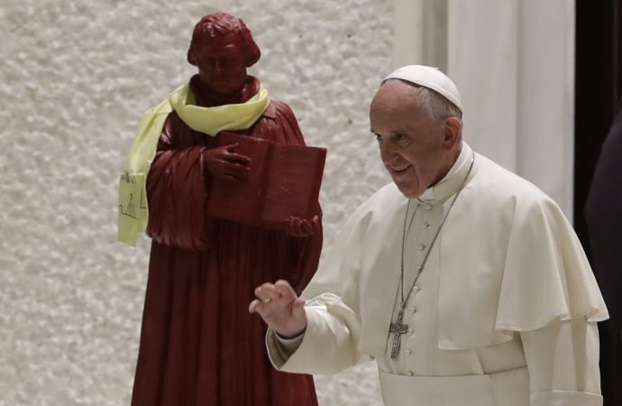 In this photo taken on Oct. 13, 2016, Pope Francis passes by a statue portraying Martin Luther as he arrives for an audience with Lutheran pilgrims at the Vatican. Pope Francis travels to Sweden next week to commemorate the split in Western Christianity 500 years ago. (Credit: AP Photo/Alessandra Tarantino.)